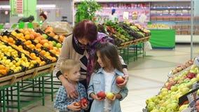 La nonna gentile dolce con i piccoli bambini compra le mele fresche nel supermercato archivi video