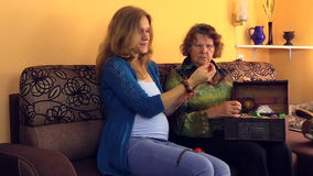 La nonna le mostra i gioielli incinti della nipote dal retro petto archivi video