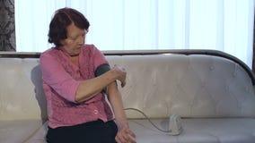 La nonna misura la sua pressione sanguigna a casa video d archivio