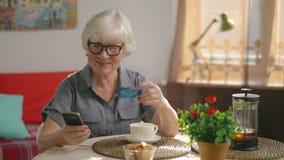 La nonna si siede ad una tavola nel suo salone accogliente e fa un acquisto archivi video