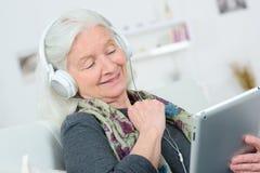 La nonna sorridente con le cuffie ascolta musica fotografia stock