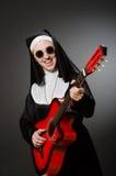 La nonne drôle avec jouer rouge de guitare Photographie stock