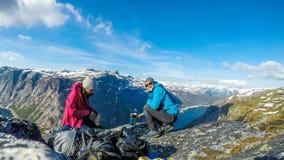 La Norvegia - una coppia che mangia prima colazione nelle montagne alte con una vista su un lago fotografia stock