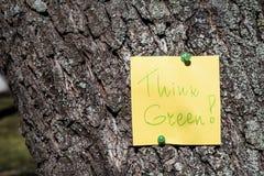 La nota de papel amarilla con piensa la muestra verde fijada en un árbol Foto de archivo libre de regalías