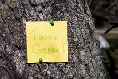 La nota de papel amarilla con piensa la muestra verde fijada en un árbol Fotografía de archivo