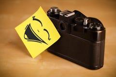 La nota de post-it con la cara sonriente sticked en cámara de la foto Fotografía de archivo libre de regalías