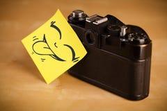 La nota de post-it con la cara sonriente sticked en cámara de la foto Foto de archivo