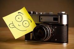 La nota de post-it con la cara sonriente sticked en una cámara de la foto Fotos de archivo