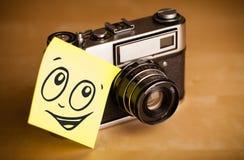 La nota de post-it con la cara sonriente sticked en cámara de la foto Imagen de archivo libre de regalías