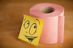 La nota de post-it con la cara sonriente sticked en el papel higiénico Imágenes de archivo libres de regalías