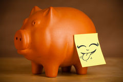La nota de post-it con la cara sonriente sticked en la hucha Imagen de archivo libre de regalías