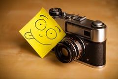 La nota de post-it con la cara sonriente sticked en una cámara de la foto Fotos de archivo libres de regalías