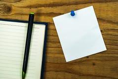 La nota del papel en blanco sobre el fondo de madera con el perno azul y el diario reservan Foto de archivo libre de regalías