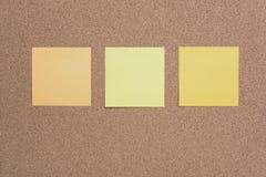La nota o los posts pegajosos está en la cartelera del boletín del corcho fotografía de archivo libre de regalías