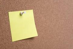La nota o los posts pegajosos está en la cartelera del boletín del corcho foto de archivo