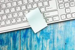 La nota pegajosa está en el teclado de ordenador Fotos de archivo libres de regalías