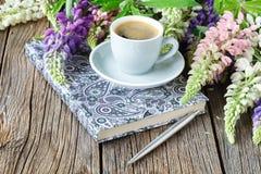 La note avec un stylo et une tasse de café, lupins fleurit sur la table en bois Image libre de droits