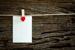 La note de papier blanc accrochant par le coeur rouge coupe sur le fond en bois Image libre de droits
