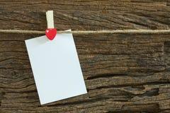 La note de papier blanc accrochant par le coeur rouge coupe sur le fond en bois Photo libre de droits