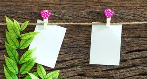 La note de papier blanc accrochant par le coeur rouge coupe sur le fond en bois Photos stock