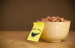 La note de post-it avec le visage souriant sticked sur le bol de céréale image stock