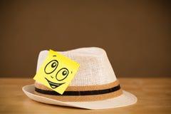 La note de post-it avec le visage souriant sticked sur le chapeau photos libres de droits