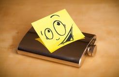 La note de post-it avec le visage souriant sticked sur le flacon de hanche image libre de droits