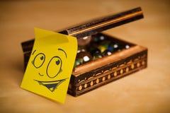 La note de post-it avec le visage souriant sticked sur la boîte à bijoux Photos stock
