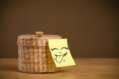 La note de post-it avec le visage souriant sticked sur la boîte à bijoux photo libre de droits
