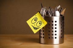 La note de post-it avec le visage souriant sticked sur la caisse de couverts Images stock