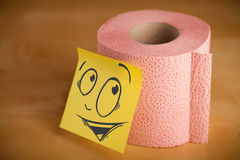 La note de post-it avec le visage souriant sticked sur le papier hygiénique Images libres de droits