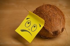 La note de post-it avec le visage souriant sticked sur la noix de coco photo stock