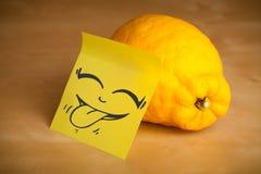 La note de post-it avec le visage souriant sticked sur un citron Photo libre de droits