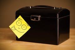 La note de post-it avec le visage souriant sticked sur une boîte à bijoux Images libres de droits