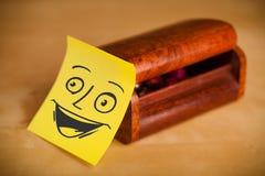 La note de post-it avec le visage souriant sticked sur une boîte à bijoux Image stock