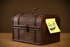 La note de post-it avec le visage souriant sticked sur une boîte à bijoux Photos libres de droits