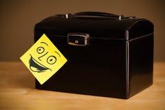 La note de post-it avec le visage souriant sticked sur une boîte à bijoux Photographie stock