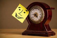 La note de post-it avec le visage souriant sticked sur une horloge photo stock