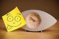 La note de post-it avec le visage souriant sticked sur une horloge photos stock