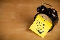 La note de post-it avec le visage souriant sticked sur une horloge images stock