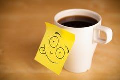La note de post-it avec le visage souriant sticked sur une tasse images stock