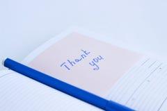 La note sur le papier VOUS REMERCIENT Image stock