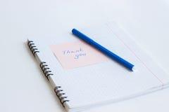 La note sur le papier VOUS REMERCIENT Photo stock