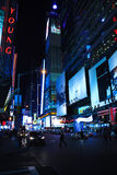 La notte ha sparato di una via con gli edifici alti pieni delle insegne al neon dentro Fotografia Stock