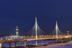 La notte nella città, ponte dell'inverno di cavo ha attraversato il fiume congelato Fotografia Stock