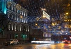 La notte nella grande città, le automobili che viaggiano sulla strada principale e splende una luce d'abbaglio Città, Kiev - dice fotografie stock libere da diritti