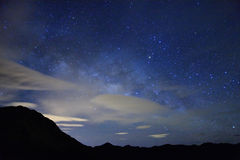 La notte stellata stupefacente accompagna con la montagna illustrazione di stock