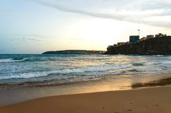 La notte sulla spiaggia della città ha fiancheggiato dalle costruzioni di appartamento alte Fotografie Stock Libere da Diritti