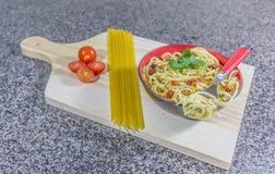 La nouille en ail et pétrole, a servi dans une cuvette avec le lard et les tomates photo libre de droits