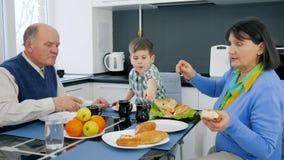 La nourriture, la grand-maman et le grand-père faits maison de retraité avec le petit-fils mangent le repas délicieux banque de vidéos